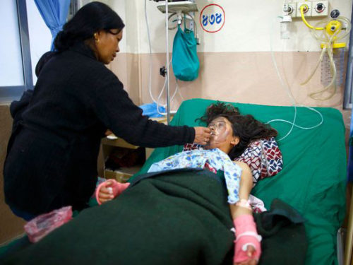 Sangita Magar's mother feeds her during her hospital stay following an acid attack